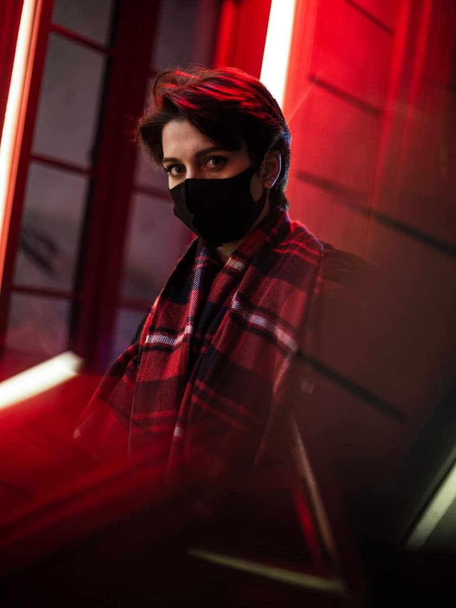 woman in red and black plaid scarf and black mask